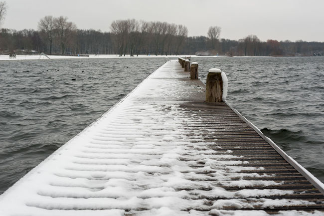 Floating wooden bridge on a lake under the snow, Rotterdam, Netherlands Floating Bridge Beauty In Nature Cold Temperature Day Nature No People Outdoors River Scenics Snow Tree Water Winter