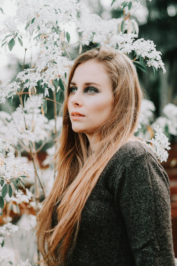 Portrait of beautiful young woman standing by flowering plant