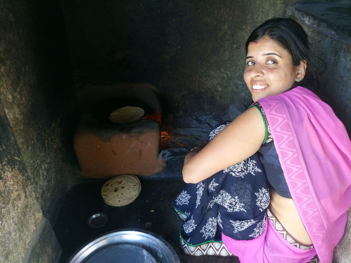 Smiling woman cooking chapatti at kitchen