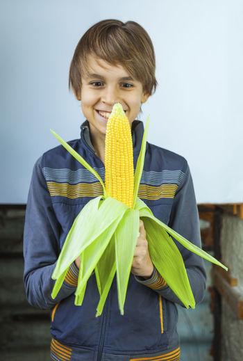 Teenager boy eating boiled corn cob Teenager Boy Eating Boiled Corn Cob