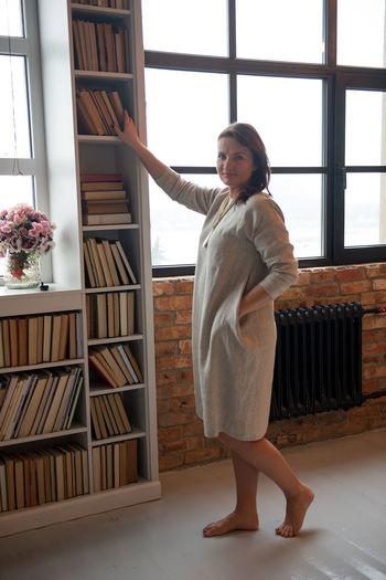 Beautiful Dress Barefoot Barefoot Lifestyle Beautiful Woman Bookshelf Clothesline Day Full Length Home Interior Indoors  Lifestyles Linen Model One Person One Woman Only People Real People Shelf Standing Summer Fashion Summer Style Window Young Adult Young Women