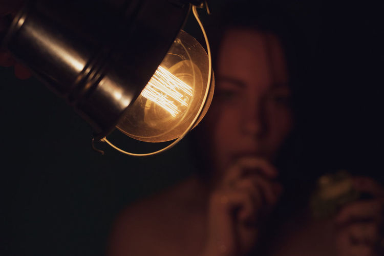 Close-up portrait of woman by illuminated light bulb