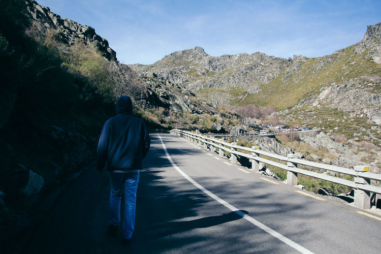 Rear view of man walking on road against mountain