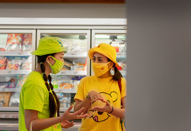 Woman holding yellow while standing in store