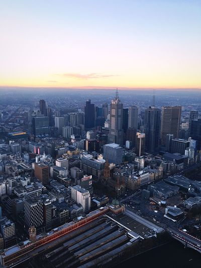 Aerial View Of Modern Cityscape Against Sky During Sunset