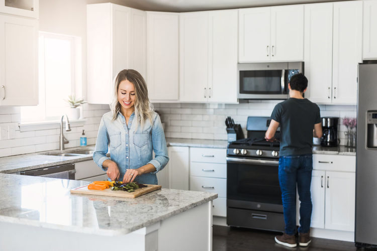 Man and woman standing in kitchen at home