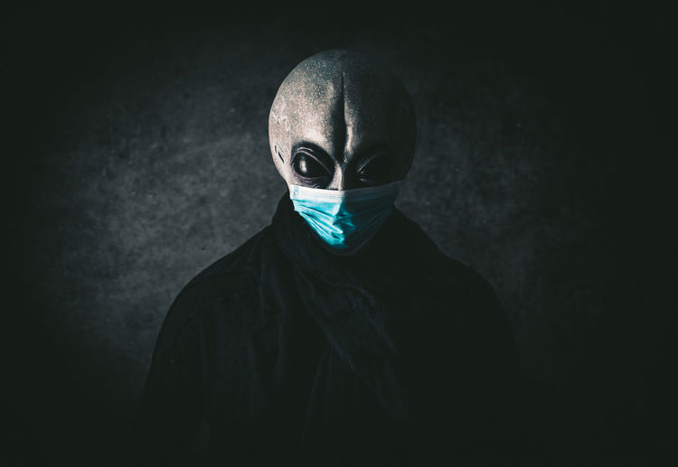 Portrait of alien wearing mask against black background