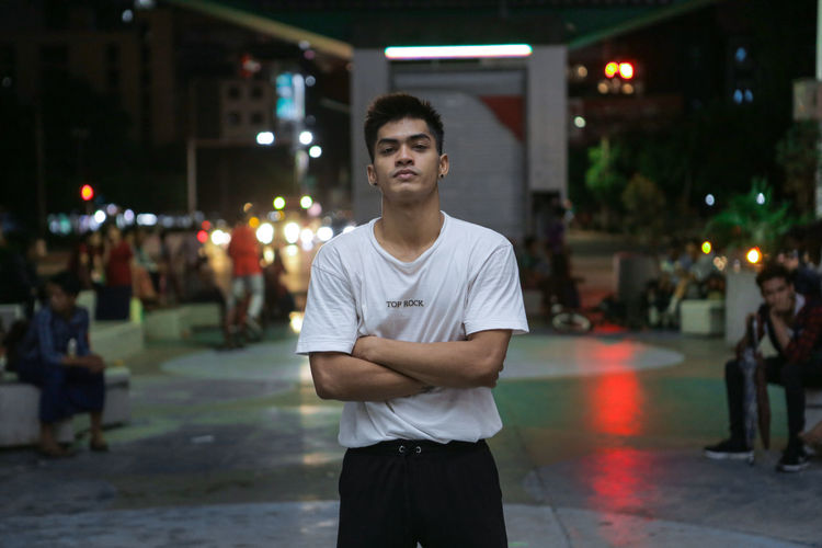 Young Man With Arms Crossed While Standing In City At Night
