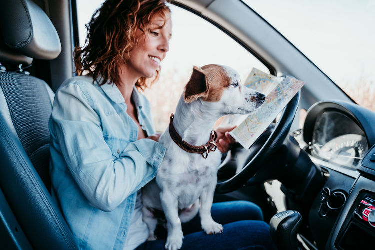 Woman with puppy analyzing map in camper trailer