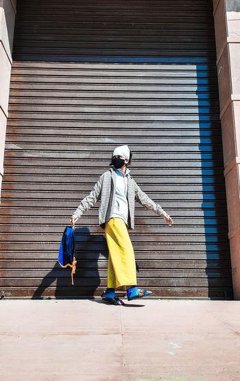 Woman standing against shutter
