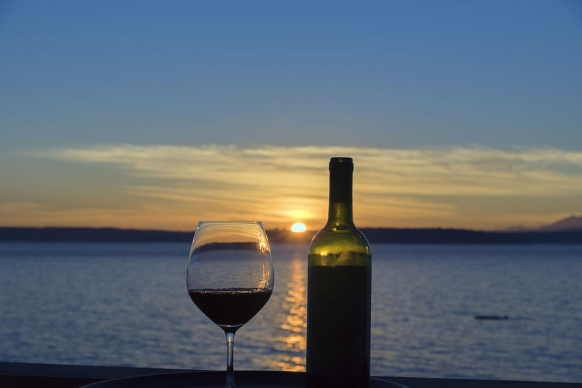 Glass of wine with bottle on seaside view deck at sunset landscape. Entertaining Tasting Travel Al Fresco Alcohol Beauty In Nature Bottle Close-up Day Drink Horizon Over Water Luxury Nature No People Outdoors Refreshment Sailing Scenics Silhouette Sky Sunset Water Wealth Management Wine Wineglass