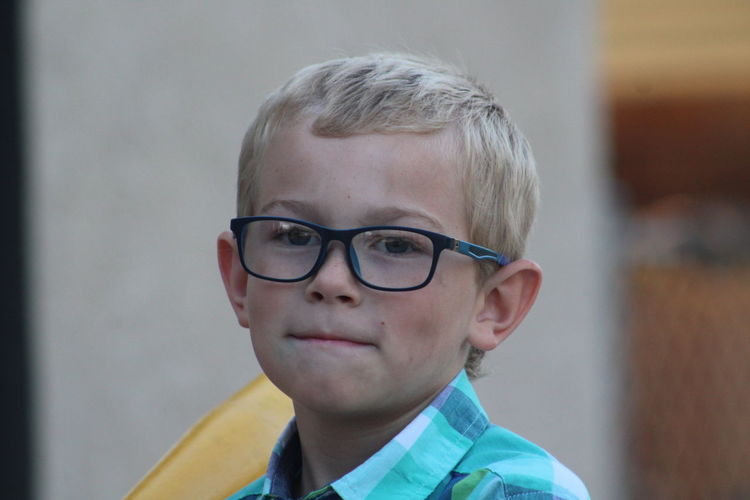 Close-up portrait of cute boy wearing eyeglasses