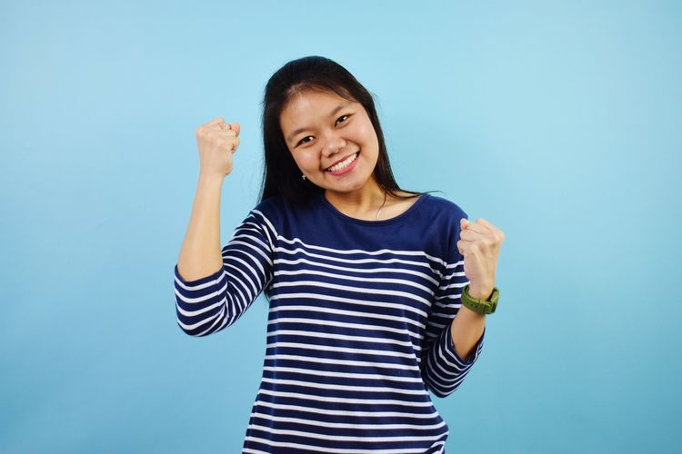 Portrait of smiling young woman against blue background
