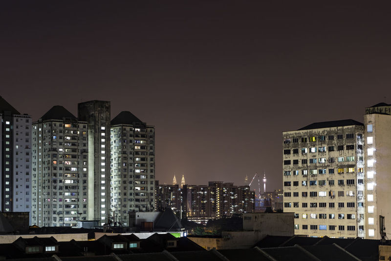 Illuminated buildings in city against clear sky at night