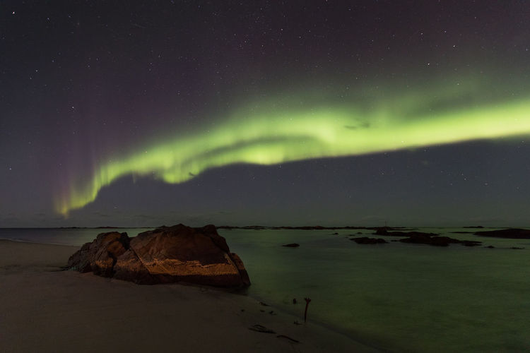 Sky illuminated by aurora borealis over beach with huge rock at low tide Astronomy Aurora Polaris Awe Beach Beauty In Nature Dramatic Sky Green Color Idyllic Illuminated Landscape Light - Natural Phenomenon Lofoten Islands Low Tide Motion Natural Phenomenon Nature Night Norwegian Sea Outdoors Rock - Object Scenics Sea Sky Space And Astronomy Star - Space The Great Outdoors - 2017 EyeEm Awards