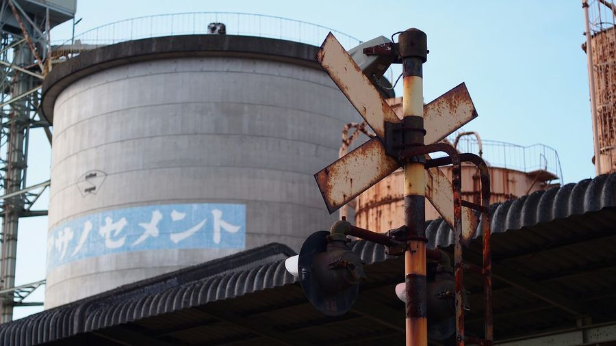 Low angle view of rusty railway signal against industry