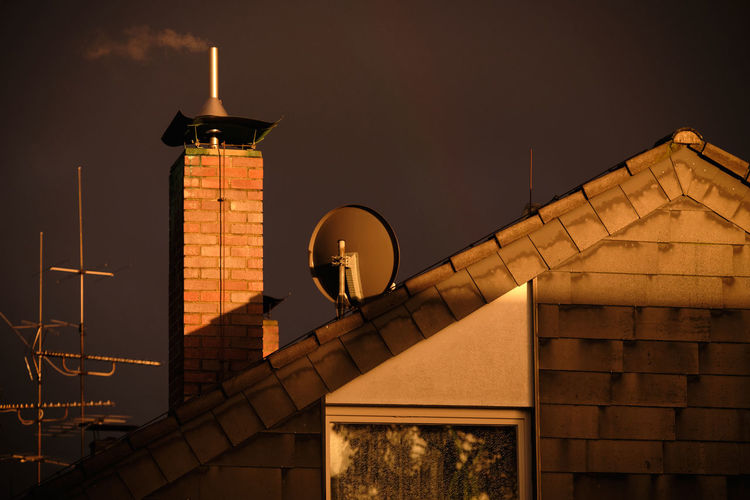 A bricked chimney with some smoke coming out together with some antennas o the roof of a house in the last rays of evening sun in front of a dramatic dark sky of a thunderstorm. Seen in Nuremberg, Germany, in April 2019 Architecture Built Structure Sky Building Exterior No People Night Low Angle View Nature Building Outdoors Communication Technology Europe Germany Nuremberg Nürnberg Thunderstorm Smoke Chimney Sunrays Sunset Storm Cloud Brick Wall Antennas Broadcasting Broadcast Television Sattelite Dish Co2 Emission Nebula Carbonated Dioxide Pollution Heating House Roof Grey Future Dramatic Illuminated Tower Dusk Travel Destinations City Antenna - Aerial Lighting Equipment Fuel And Power Generation