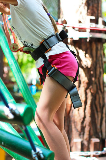 Cute girl 8 years old in adventure rope town, selective focus Arts Culture And Entertainment Casual Clothing Clothing Day Festival Focus On Foreground Girl Human Leg Incidental People Leisure Activity Lifestyles Midsection Outdoors Real People Rope Town Shorts Side View Three Quarter Length
