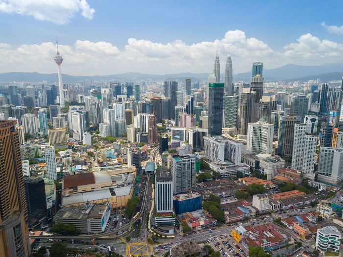 Petronas towers amidst cityscape against sky