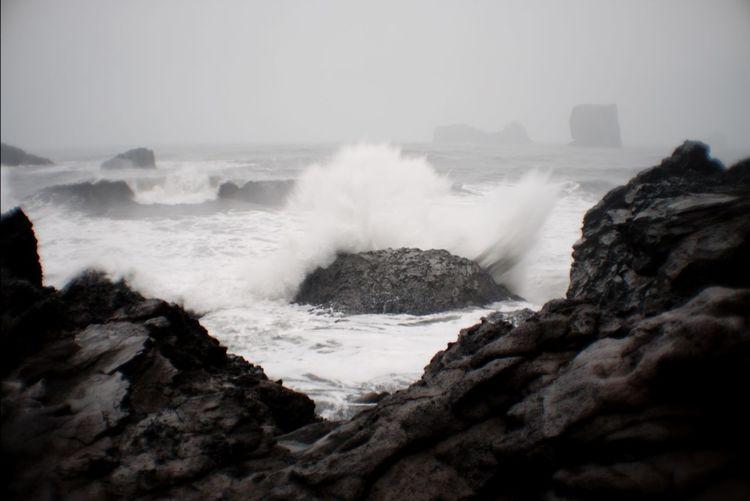 Wave hitting a grey rock