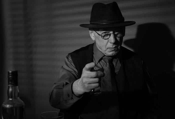 Film Noir reloaded: The dirty old detective in his bureau talking to a new client Acting Adult Hat Alcohol Bottle Close-up Day Detective Front View Hat Holding Indoors  Monochrome Old Person Old Person Sitting One Man Only One Person Portrait Real People Studio Shot Suit