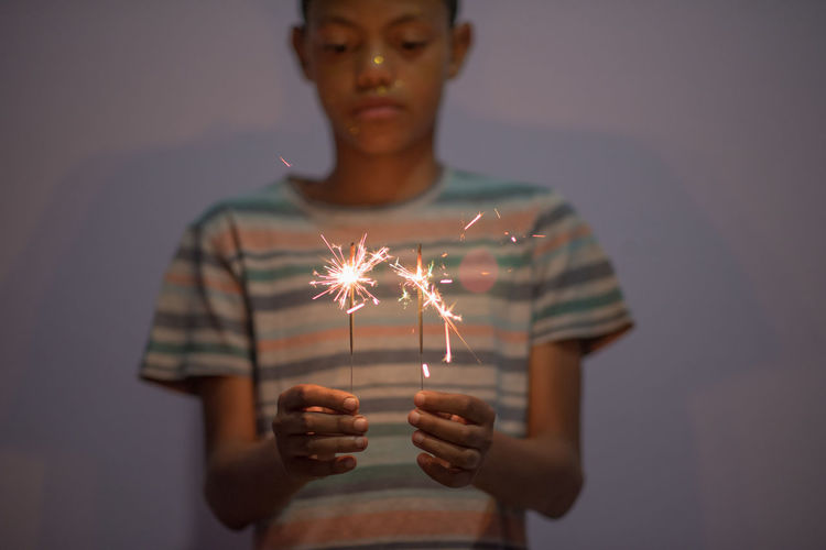 fire Blurred Motion Burning Casual Clothing Celebration Firework Focus On Foreground Front View Glowing Holding Illuminated Indoors  Leisure Activity Lifestyles One Person Portrait Real People Sparkler Sparks Standing Teenager Waist Up Young Adult