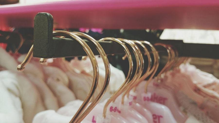 Close-up of coathangers hanging on rack at store