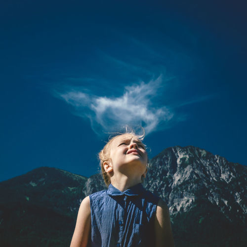 Girl looking up at blue sky with mountain backdrop and cloud above