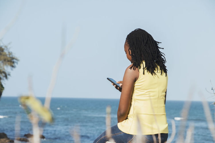 Rear view of woman using mobile phone by sea against sky