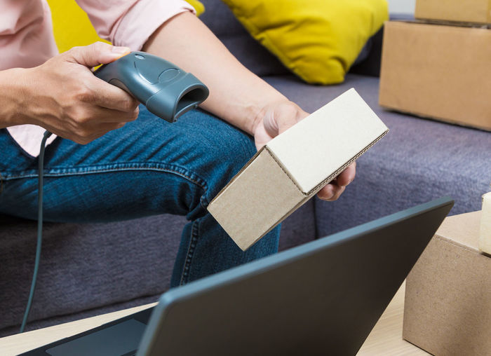 Midsection of man scanning boxes while sitting on sofa at home