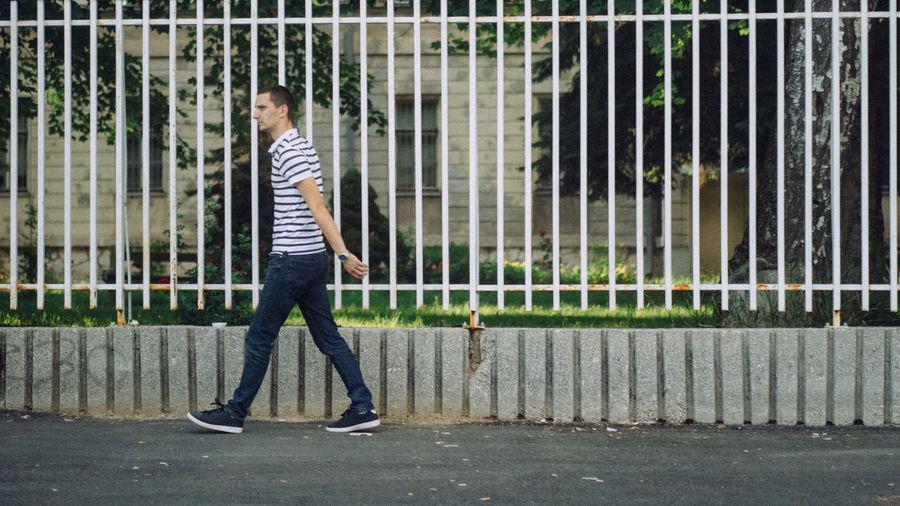 Full length of man standing on sidewalk in city