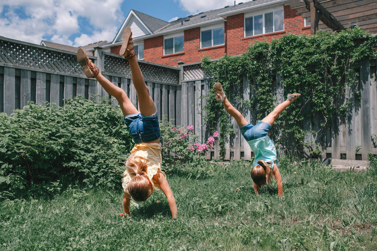 Full length of girls doing handstand in yard
