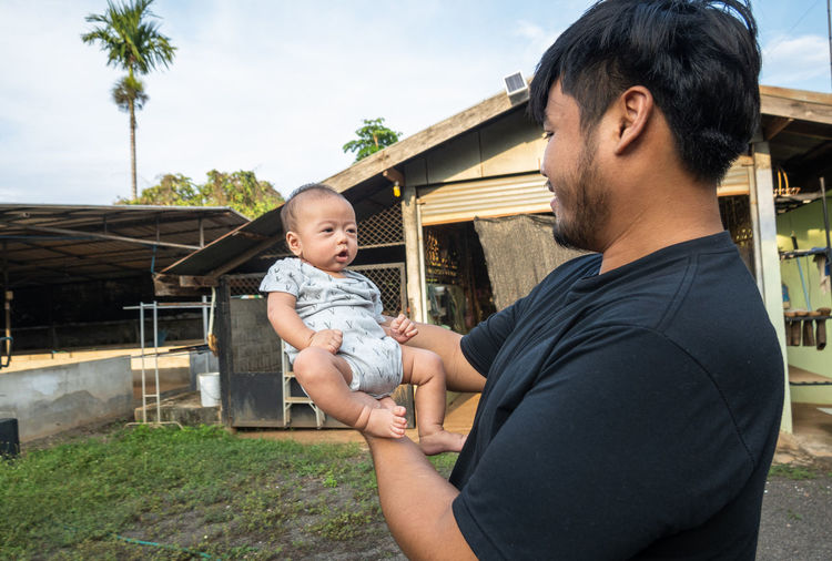 Father and son holding baby while standing outdoors