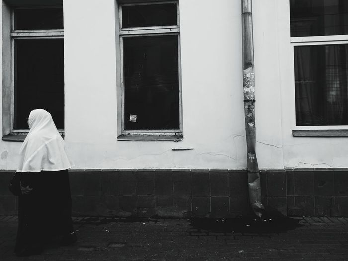 Rear view of boy standing against window