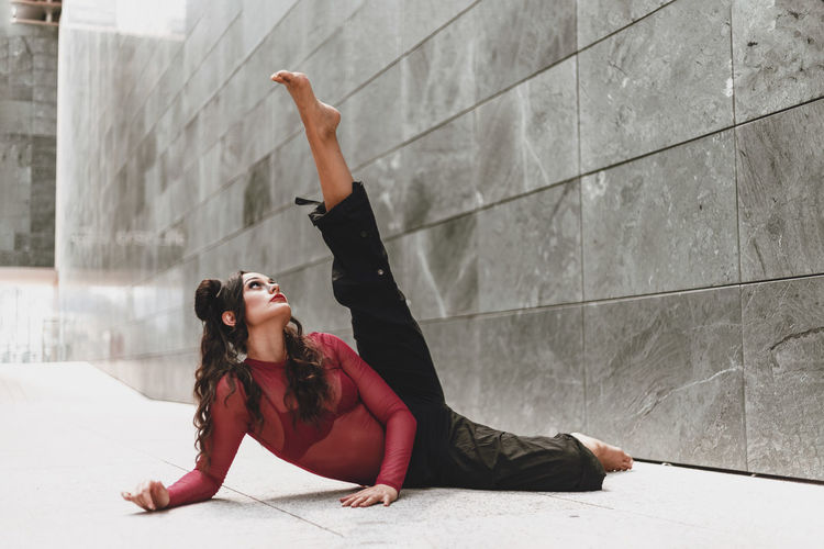Full length of woman dancing on floor against wall