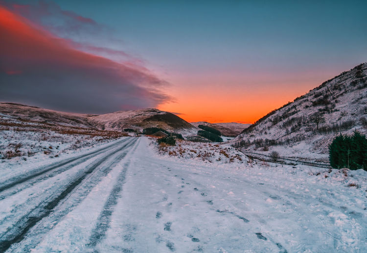 Snow covered road against sky during sunset