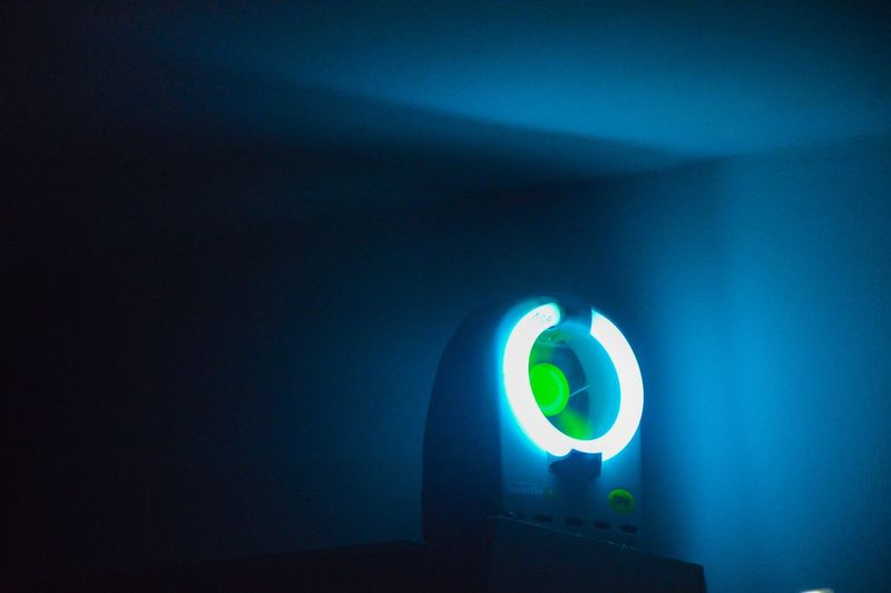 Illuminated electric light on blue wall