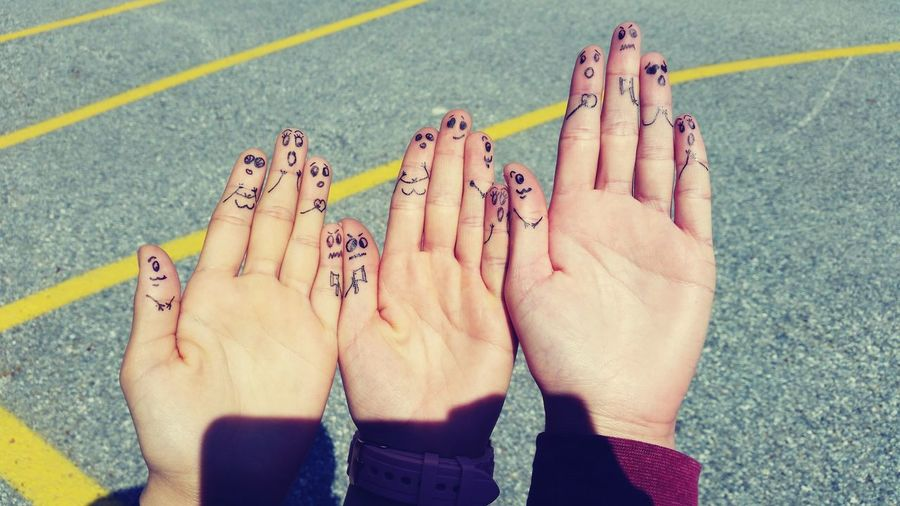 Cropped Hands Of Friends With Drawing On Fingers Against Road During Sunny Day