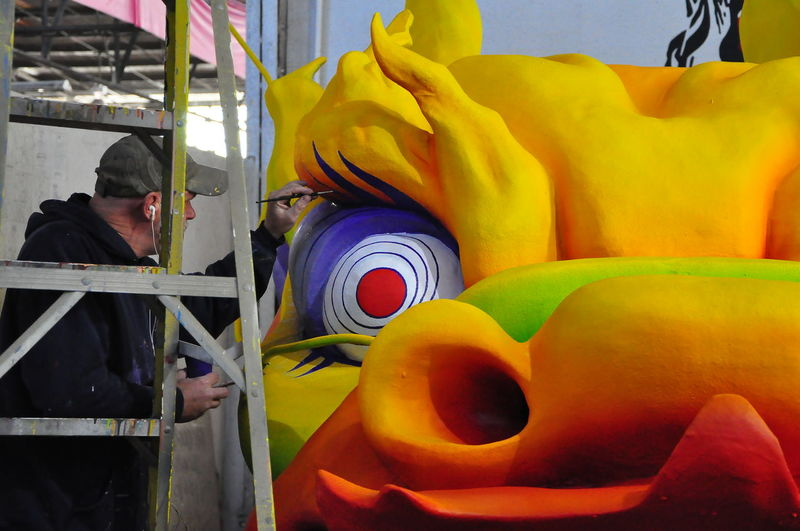 Man giving the finishing touches to a Mardi Gras float - the Mardi Gras Museum - New Orleans, USA Mardi Gras Float Workman Bulbous Eyes Day Freshness Indoors  Mardi Gras Museum Men Multi Colored One Person Painter - Artist People Real People Yellow Yellow Face Paint The Town Yellow