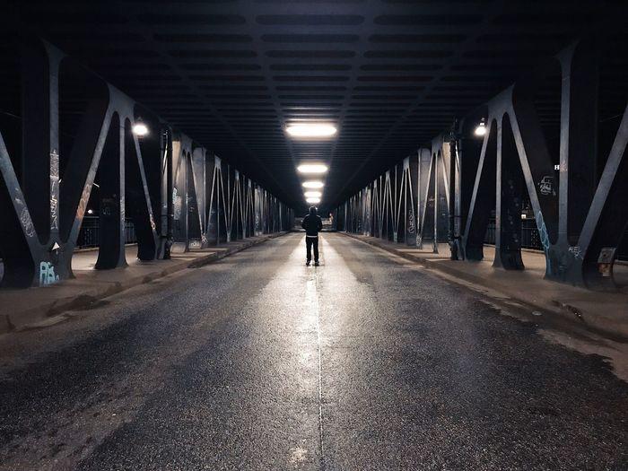 Rear view of man walking on illuminated road at night