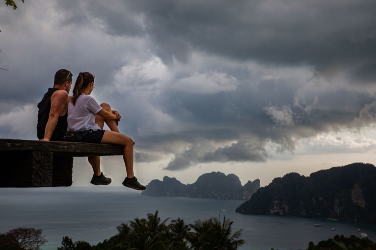 Couple sitting at observation point with sea in background against cloudy sky