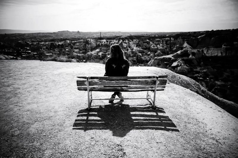 Rear view of woman sitting on bench