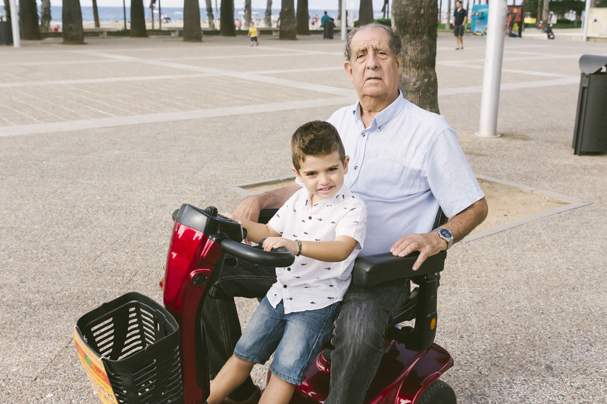 Grangfather and child on a motorized chair Grandfather Bonding Boys Care Casual Clothing Child Childhood Day Electricity  Family Front View Grandchild Innocence Leisure Activity Lifestyles Males  Men Motorized Outdoors Real People Sitting Son Three Quarter Length Togetherness Transportation Two People