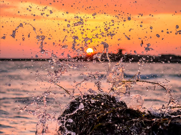 Water drops on glass window during sunset