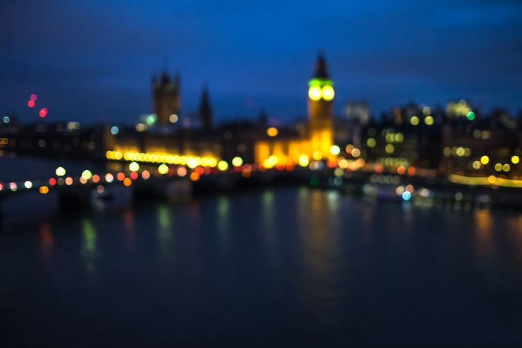 Defocused image of illuminated big ben and city by thames river at dusk
