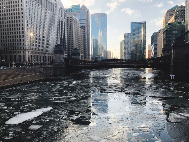 Melting ice floating down river Architecture City Building Exterior Skyscraper Built Structure Water Modern Waterfront Cityscape Winter River Cold Temperature Outdoors Sky Urban Skyline Day No People