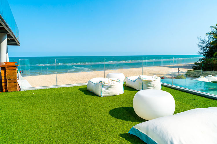 Lounge chairs by swimming pool on beach against clear sky