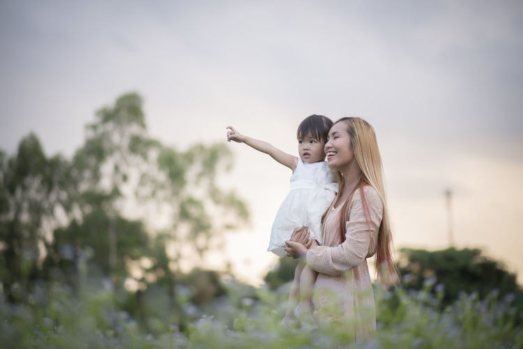 Mother carrying daughter while standing against sky