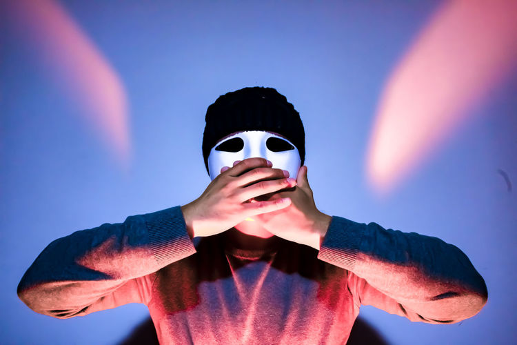 Close-up of man covering mouth while wearing mask against illuminated wall