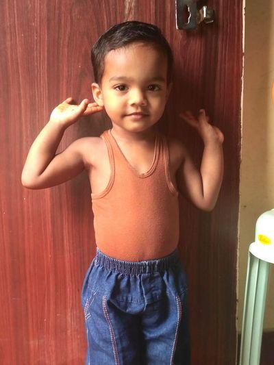 Portrait of cute boy standing against door at home